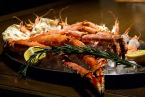 plate of crab legs with lemon and butter.