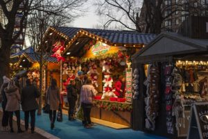 An outdoor Christmas market, featuring string lights, garland, and a store called Santa's Workshop.